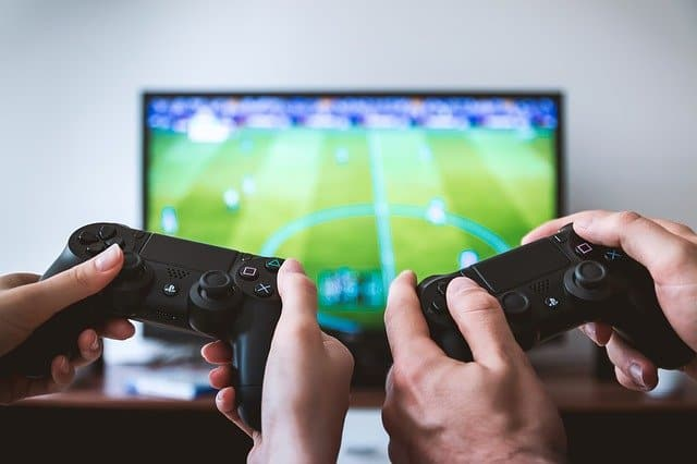 two hands with video game controllers