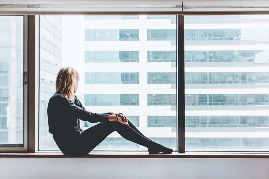 woman staring out a window in lockdown
