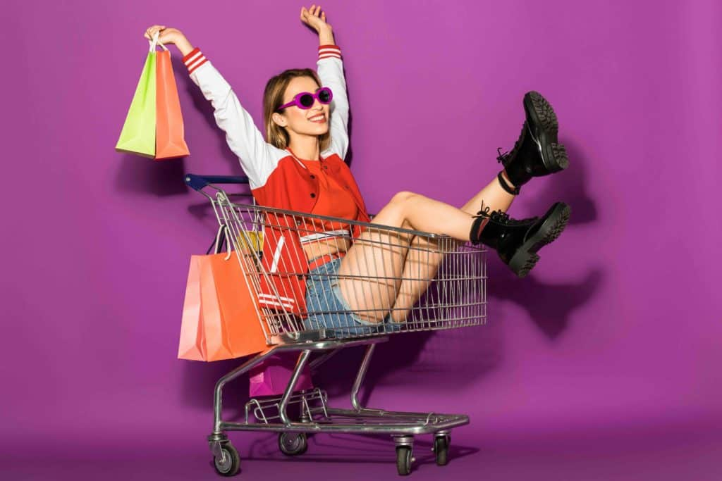 woman sitting in shopping cart with shopping bags