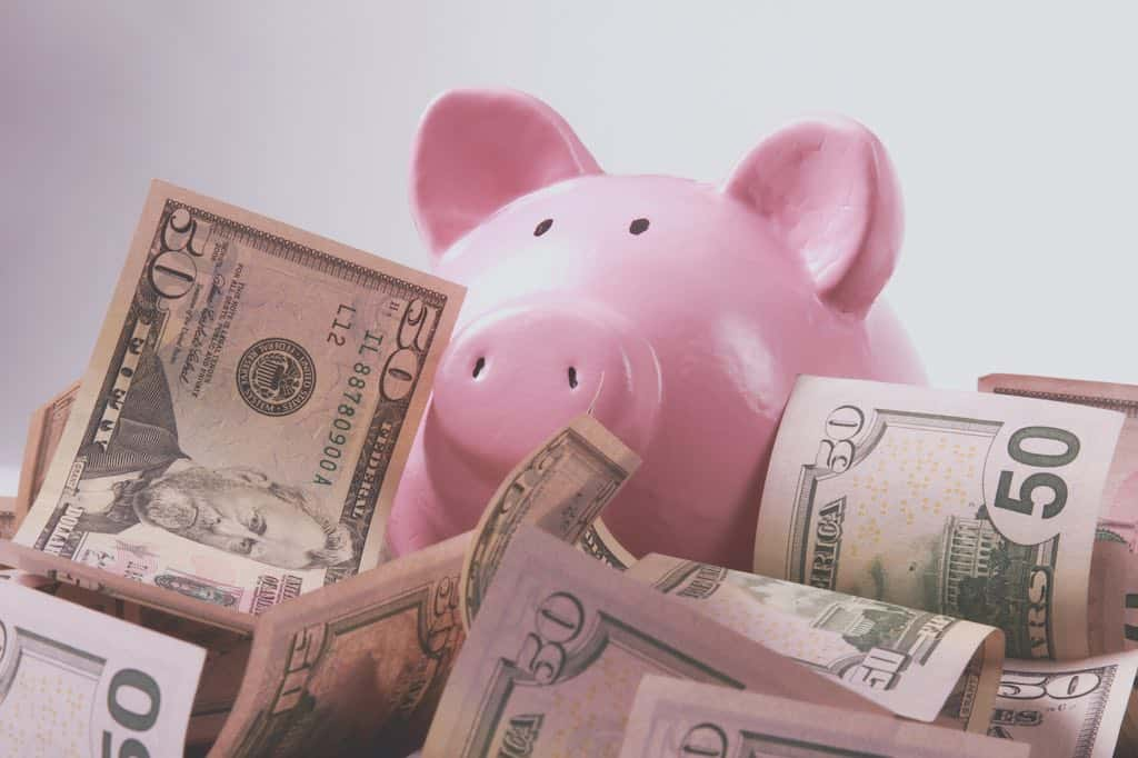Piggy bank style money box on background with money american hundred dollar bills