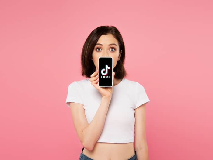 young woman holding smartphone with TikTok