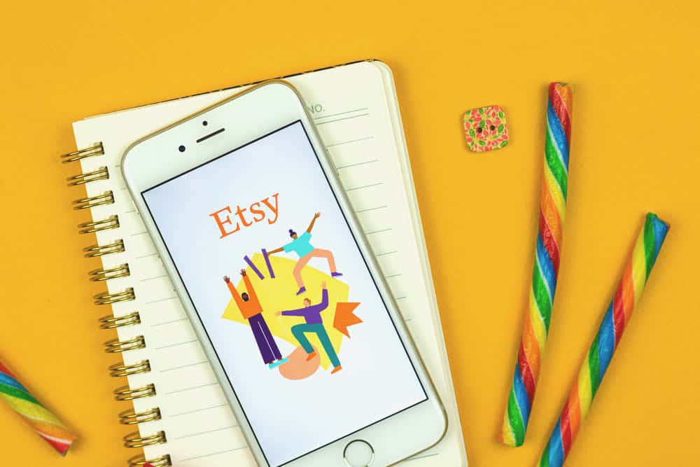 etsy app on phone and notebook paper
